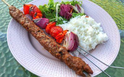 Kryddiga färsspett och röda grönsaksspett på grillen
